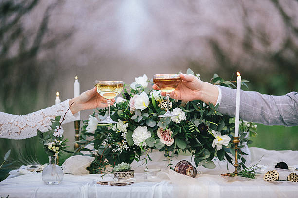 raising glasses with champagne at the wedding table - mariage photos et images de collection