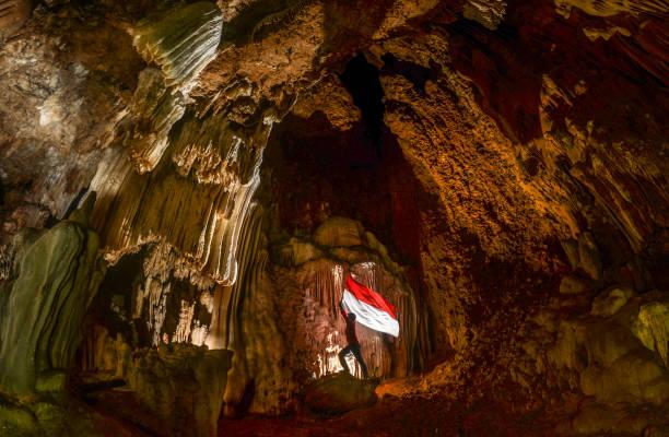 levantando a bandeira indonésia na antiga caverna em rammang-rammang - bandeira da indonesia - fotografias e filmes do acervo