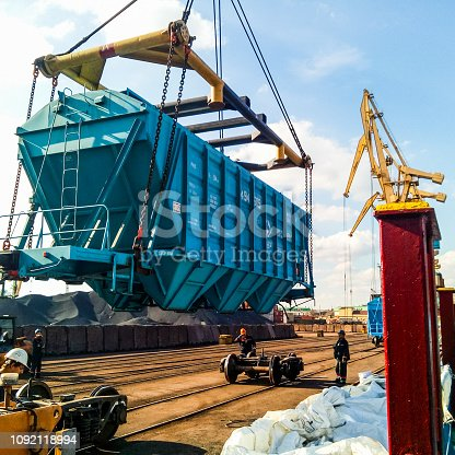 istock Raising the hopper car for unloading on a cargo ship. Lifting operations in the port. 1092118994