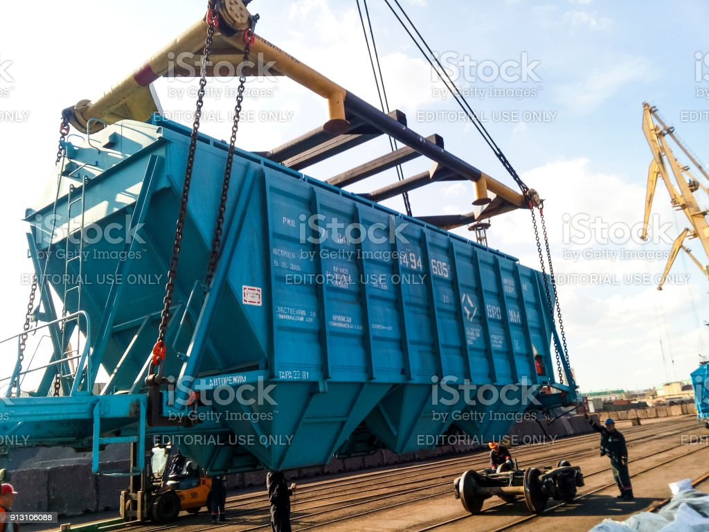 Raising the hopper car for unloading on a cargo ship. Lifting operations in the port. stock photo
