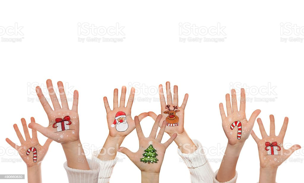 Raising up children's hands and painted symbols. Santa, snowman etc. stock photo