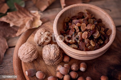 Raisin - dried grape fruits in wood bowl with walnut and hazelnut at wooden autumn background. Close-up, selective focus