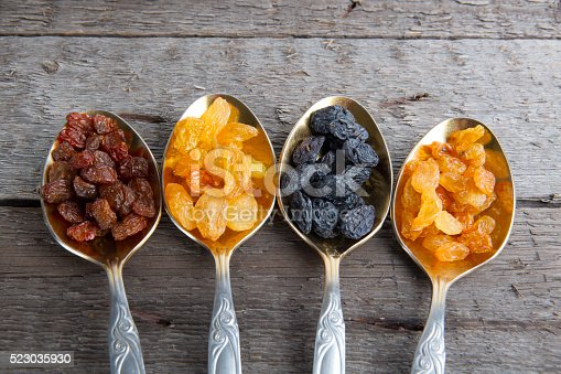 istock Raisins in metal spoons on wooden table 523035930