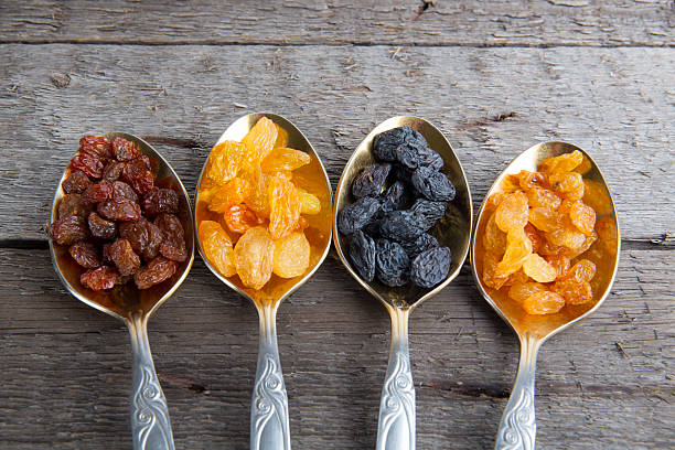 raisins in metal spoons on wooden table - dried fruit stock photos and pictures