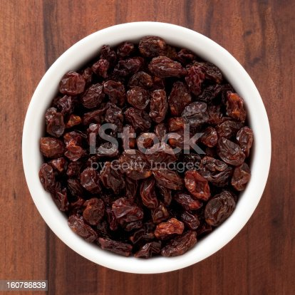 Top view of white bowl full of raisins