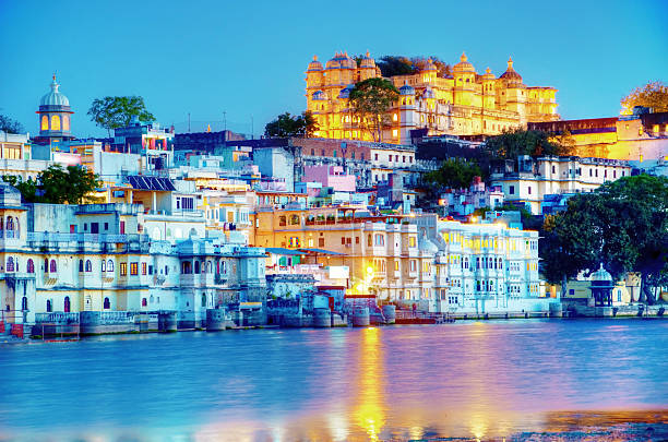 Rajasthan, India, Udaipur fortress by night 2 Rajasthan, India, Udaipur fortress by night with lake-Pichhola in front.  udaipur stock pictures, royalty-free photos & images