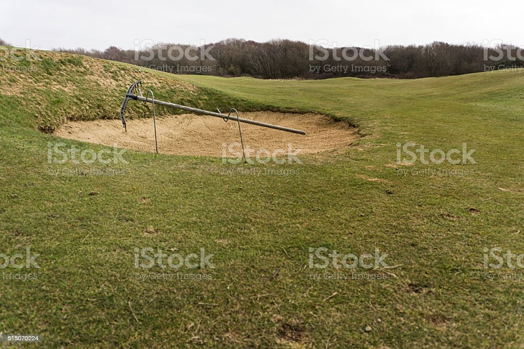 Rake at the side of a golf bunker stock photo