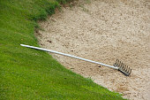 Rake in golf sand bunker on the border with green grass
