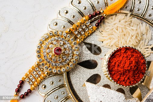 istock Raksha Bandhan - Rakhi and gift with sweet kaju katli or mithai and rice grains and kumkum in a decorative plate. Traditional Indian wrist band which is a symbol of love between Brothers and Sisters. 826449952