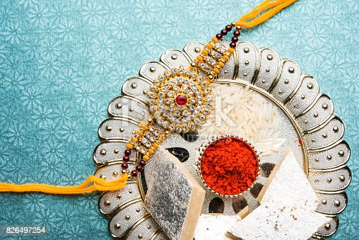 istock Raksha Bandhan - Rakhi and gift with sweet kaju katli or mithai and rice grains and kumkum in a decorative plate. Traditional Indian wrist band which is a symbol of love between Brothers and Sisters. 826497254