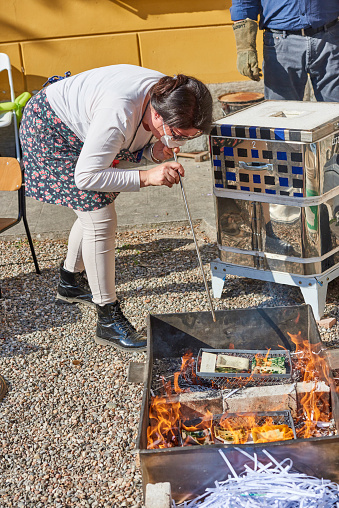 Solaro, Italy - April 10, 2016: a woman, taking part to a public ceramic making class, blowing air from a tube into pieces of raku ceramics during flame glazing process, also known as Raku Firing Process.