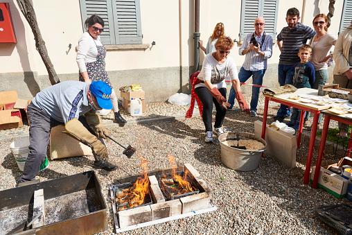 Solaro, Italy - April 10, 2016: a man, taking part to a public ceramic making class, arrange piece of ceramics into metallic basket, during flame glazing process, also known as Raku Firing Process.