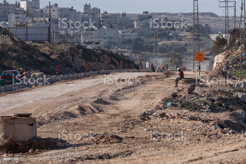 RAM, Palestina, 12 de janeiro de 2011: Os trabalhadores estão construindo uma nova estrada na paisagem seca e desarrumada da Palestina na Ram. - Foto de stock de Adulto royalty-free