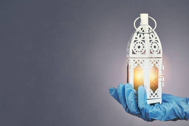 Ramadan 2020 in quarantine Hand in protective medical gloves holding traditional Arabic lantern with middle-eastern carving. Celebrating Holly month Ramadan 2020 in quarantine. A doctor celebrates Ramadan in hospital muziekfestival stock pictures, royalty-free photos & images