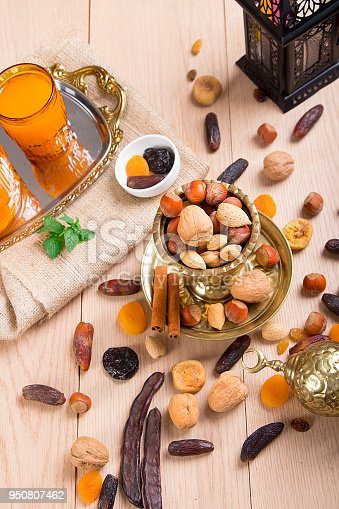 692990508 istock photo Ramadan Atmosphere - Collection of Ramadan Fruits and Nuts with Lantern on wooden table 950807462