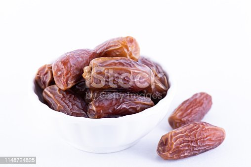 878724422 istock photo Ramadan food and drinks concept. Close up dates fruit on white background. 1148724825