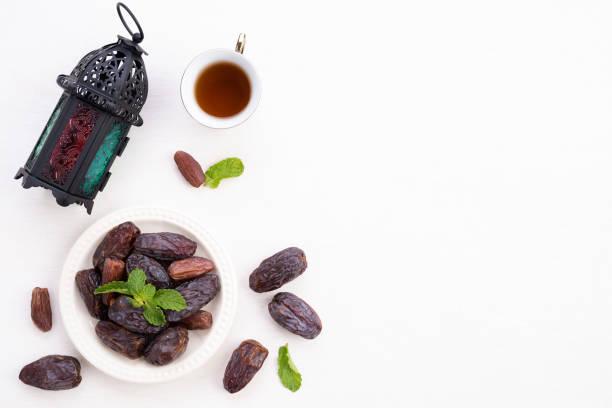 Ramadan Speisen und Getränke Konzept. Ramadan Lantern mit Tee, datiert Obst-, Trauben-und Minzblätter auf einem weißen Holztisch. Topansicht, Flat lay. – Foto