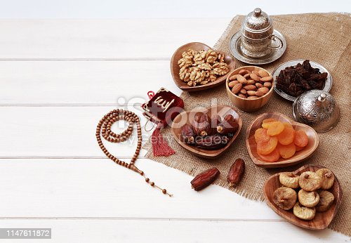 689618578 istock photo Ramadan iftar party concept. Islamic holy book Quran and rosary beads with delicious dates, dried figs, dried apricots, walnuts, almonds, raisins on bamboo plates on a white wooden table background. 1147611872