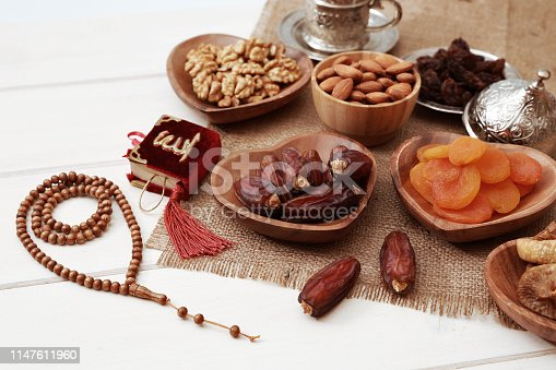 689618578 istock photo Ramadan iftar party concept. Islamic holy book Quran and rosary beads with delicious dates, dried figs, dried apricots, walnuts, almonds, raisins on bamboo plates on a white wooden table background. 1147611960