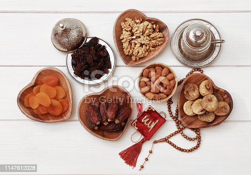 689618578 istock photo Ramadan iftar party concept. Islamic holy book Quran and rosary beads with delicious dates, dried figs, dried apricots, walnuts, almonds, raisins on bamboo plates on a white wooden table background. 1147612028