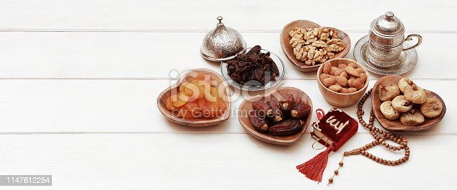 689618578 istock photo Ramadan iftar party concept. Islamic holy book Quran and rosary beads with delicious dates, dried figs, dried apricots, walnuts, almonds, raisins on bamboo plates on a white wooden table background. 1147612254