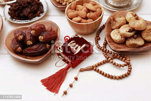 689618578 istock photo Ramadan iftar party concept. Islamic holy book Quran and rosary beads with delicious dates, dried figs, dried apricots, walnuts, almonds, raisins on bamboo plates on a white wooden table background. 1147612400