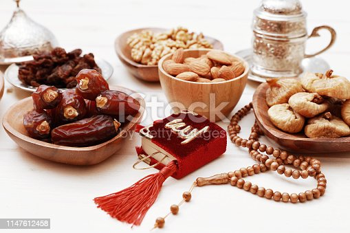 689618578 istock photo Ramadan iftar party concept. Islamic holy book Quran and rosary beads with delicious dates, dried figs, dried apricots, walnuts, almonds, raisins on bamboo plates on a white wooden table background. 1147612458