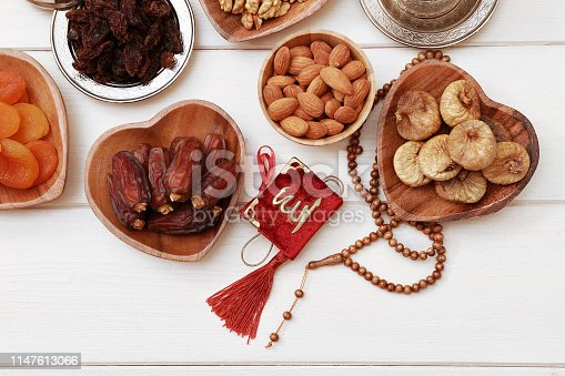 689618578 istock photo Ramadan iftar party concept. Islamic holy book Quran and rosary beads with delicious dates, dried figs, dried apricots, walnuts, almonds, raisins on bamboo plates on a white wooden table background. 1147613066