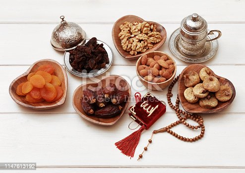 689618578 istock photo Ramadan iftar party concept. Islamic holy book Quran and rosary beads with delicious dates, dried figs, dried apricots, walnuts, almonds, raisins on bamboo plates on a white wooden table background. 1147613192