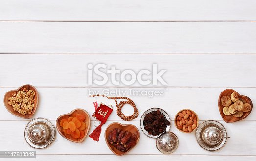 689618578 istock photo Ramadan iftar party concept. Islamic holy book Quran and rosary beads with delicious dates, dried figs, dried apricots, walnuts, almonds, raisins on bamboo plates on a white wooden table background. 1147613349