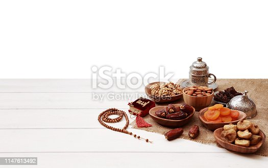 689618578 istock photo Ramadan iftar party concept. Islamic holy book Quran and rosary beads with delicious dates, dried figs, dried apricots, walnuts, almonds, raisins on bamboo plates on a white wooden table background. 1147613492