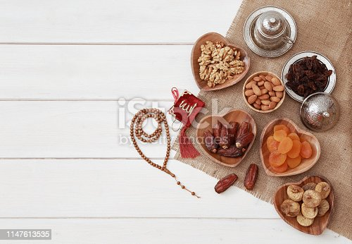 689618578 istock photo Ramadan iftar party concept. Islamic holy book Quran and rosary beads with delicious dates, dried figs, dried apricots, walnuts, almonds, raisins on bamboo plates on a white wooden table background. 1147613535