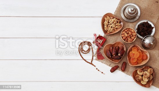689618578 istock photo Ramadan iftar party concept. Islamic holy book Quran and rosary beads with delicious dates, dried figs, dried apricots, walnuts, almonds, raisins on bamboo plates on a white wooden table background. 1147613596