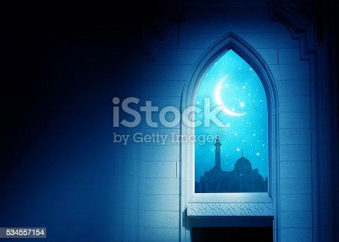 istock Ramadan Kareem background. .Mosque window with shiny crescent mo 534557154
