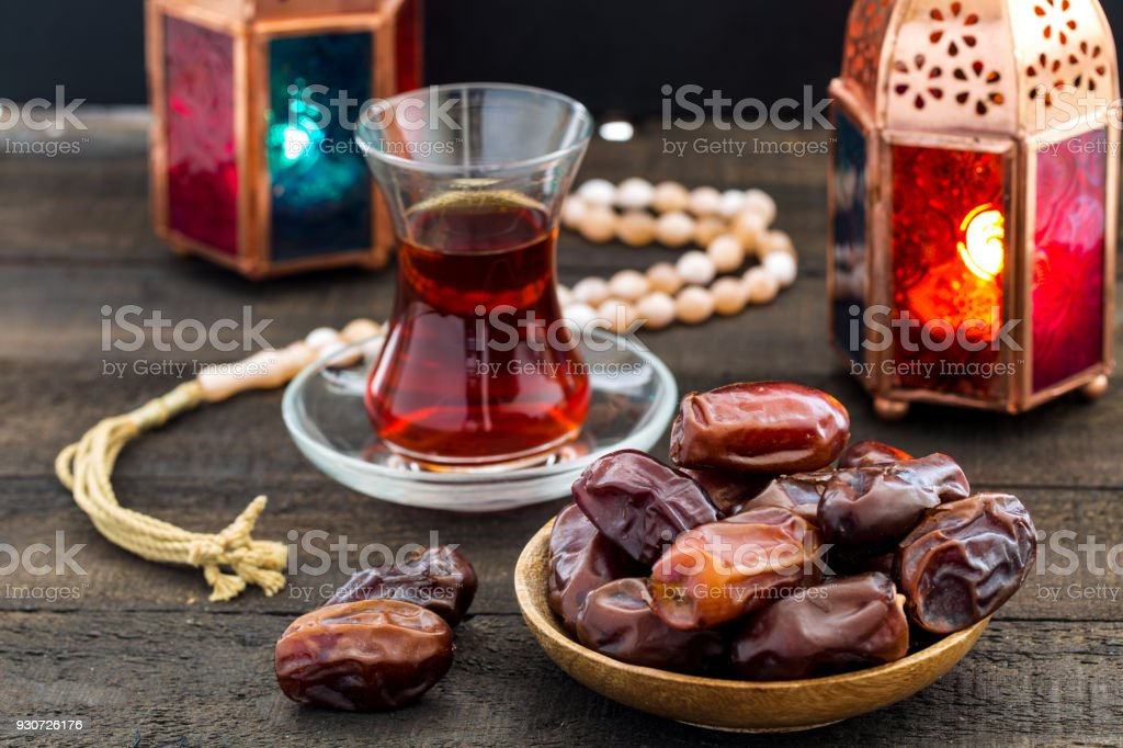 Ramadan Kareem Festive, close up of dates on wooden plate and rosary with oriental Lantern lamps and cup of black tea on wood background. Islamic Holy Month Greeting Card stock photo