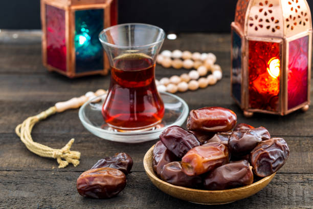 ramadan kareem festive, close up of dates on wooden plate and rosary with oriental lantern lamps and cup of black tea on wood background. islamic holy month greeting card - ramadan stock photos and pictures