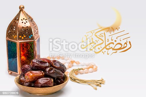 istock Ramadan Kareem Festive, close up of oriental Lantern lamp with dates on wooden plate and rosary on white background. Islamic Holy Month Greeting Card 930728826