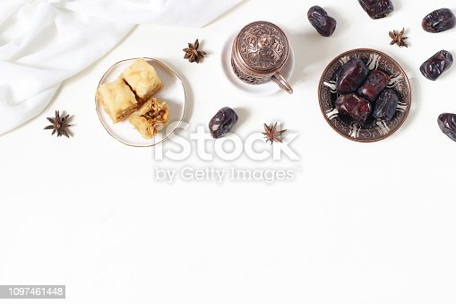 istock Ramadan Kareem greeting card, invitation. Bronze plate with dates fruit, baklava pastry, coffee cup, anise stars on white table. Iftar dinner. Eid ul Adha banner background. Muslim flat lay, top view. 1097461448