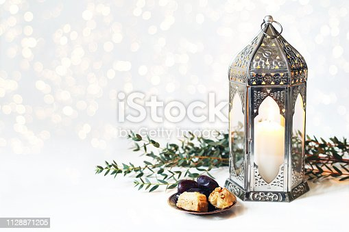 istock Ramadan Kareem greeting card, invitation. Bronze plate with dates fruit, baklava pastry, burning silver Moroccan, Arabic lantern on white table. Iftar dinner. Glittering lights. Eid ul Adha background 1128871205