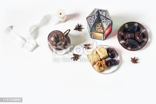 istock Ramadan Kareem greeting card, invitation. Bronze plate with dates fruit, baklava pastry, coffee cup,glowing lantern on white table. Iftar dinner. Eid ul Adha banner background. Flat lay, top view 1141246587