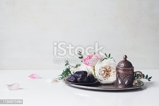 istock Ramadan Kareem greeting card, invitation. Plate with dates fruit, bronze coffee cup, pink roses and green branches on old silver tray. White table background. Muslim Iftar dinner. Eid ul Adha banner. 1134972495