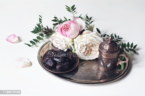 istock Ramadan Kareem greeting card, invitation. Plate with dates fruit, bronze coffee cup, pink roses and green branches on old silver tray. White table background. Muslim Iftar dinner. Eid ul Adha banner. 1136679168