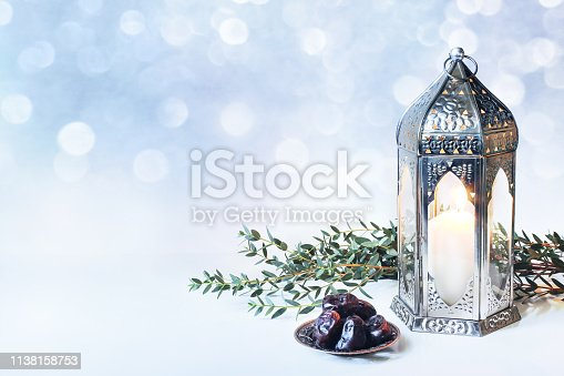 istock Ramadan Kareem greeting card, invitation. Plate with dates fruit, burning silver Moroccan, Arabic lantern and green branch on white table. Iftar dinner. Glittering lights. Eid ul Adha background. 1138158753