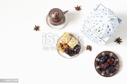 istock Ramadan Kareem greeting card, invitation. White lantern, bronze plate with dates fruit, baklava pastry, coffee cup on table. Iftar dinner. Eid ul Adha banner background. Flat lay, top view. 1148842098