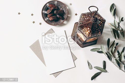 istock Ramadan Kareem mockup. Bronze plate with dates fruit, olive branches, glowing Moroccan lanternand blank greeting card on white marble table. Iftar dinner. Eid ul Adha background. Flat lay, top view. 1211298112