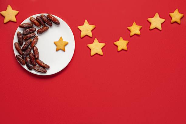 Ramadan kareem mit Datteln in Form von Halbmond angeordnet  und Sterne von Cookies auf rotem Hintergrund. Ansicht von oben – Foto