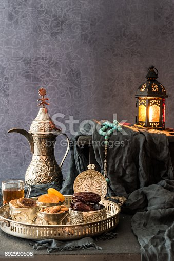 istock Ramadan kareem with premium dates,nuts and arabic tea. Festive still life with oriental ramadan lantern and iftar food concept. 692990508