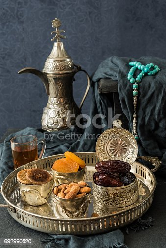 692990508 istock photo Ramadan kareem with premium dates,nuts and Arabic tea. Festive still life of iftar food concept. 692990520