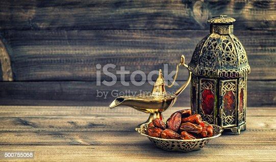 istock Ramadan lamp and dates on wooden background. Oriental lantern 500755058