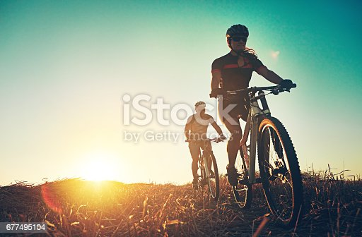 Shot of a pair of adventurous mountain bikers out on a trail on a sunny day